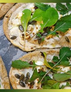 Mini-pizzas à la crème de chou-fleur, roquette et graines de courge.